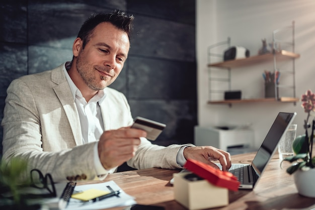 Uomini che acquistano online e utilizzano la carta di credito