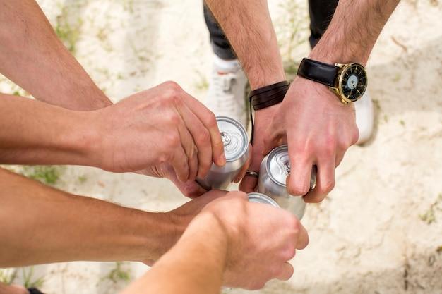 Uomini che aprono lattine di birra