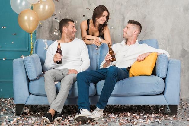 Uomini che bevono birra e parlano con la donna