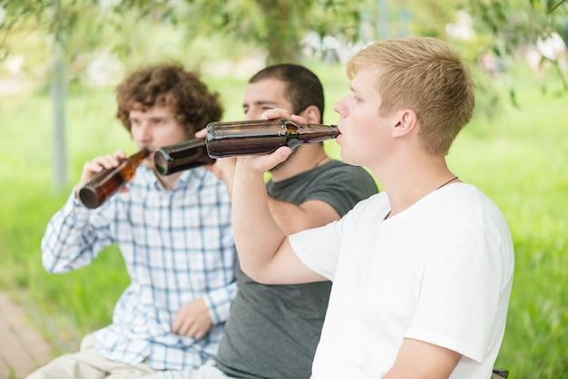 Uomini che bevono birra nel parco