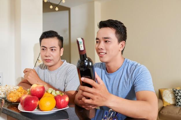Uomini che bevono vino alla festa a casa