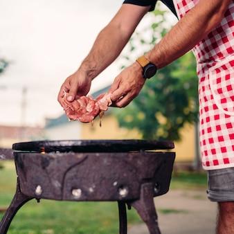 Uomini che indossano grembiule posizionando carne di pollo cruda sul barbecue