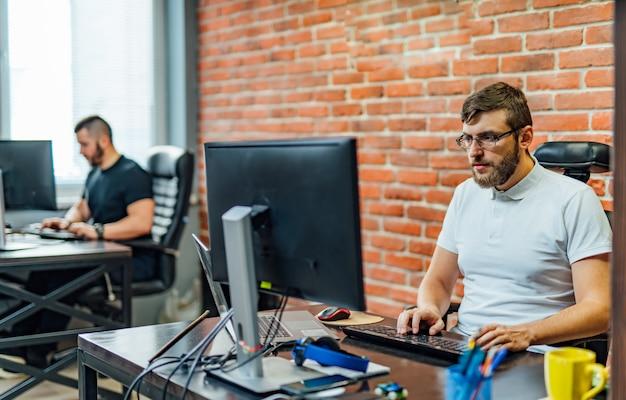 Uomini che lavorano in ufficio. uomo d'affari giovane seduto in ufficio e lavorando sul desktop