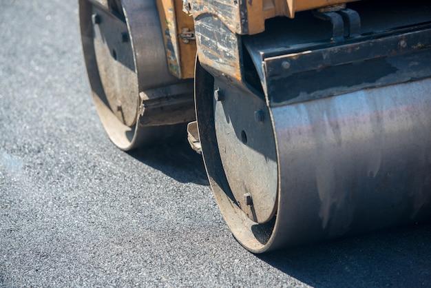 Uomini che lavorano sulla nuova strada mettendo nuovo asfalto