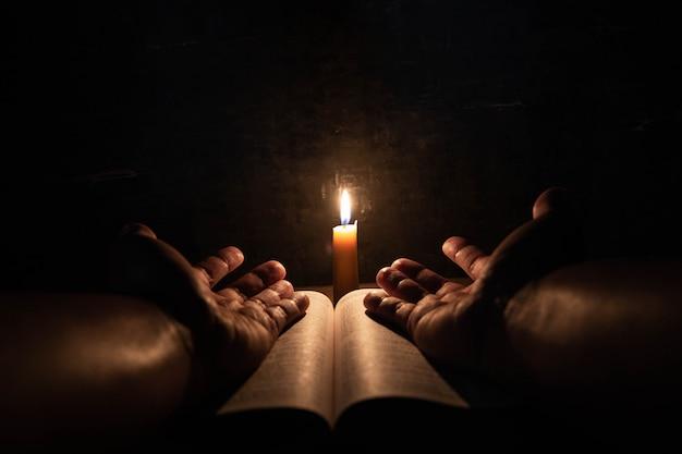 Uomini che pregano sulla bibbia nel fuoco selettivo delle candele leggere.