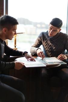 Uomini che scelgono cibo nella caffetteria insieme