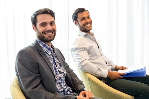 Uomini che sorridono alla macchina fotografica mentre sedendosi nell'ufficio