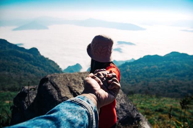 Uomini che tengono le mani donne che viaggiano verso il paesaggio di nebbia e montagna