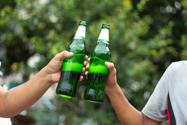 Uomini che tengono verde bottiglia di birra.