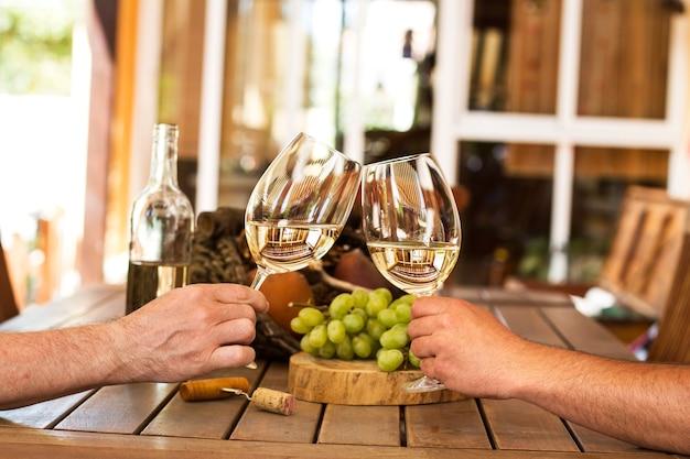 Uomini che tostano con vino bianco su un tavolo di legno con uva verde