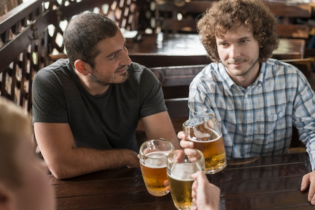 Uomini con alcolici che riposano al tavolo da bar