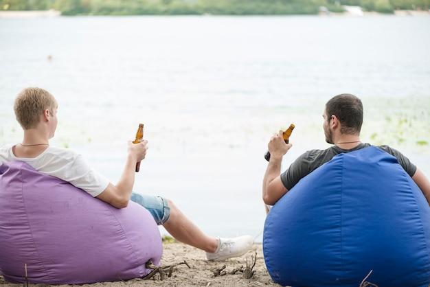 Uomini con birra rilassante su sacchi di fagioli