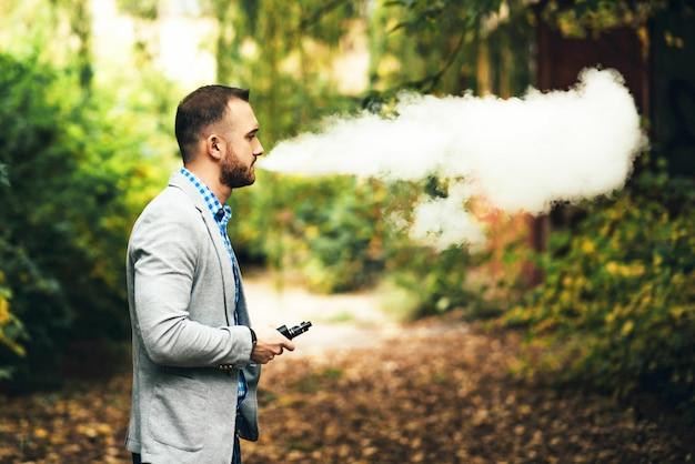 Uomini con la barba che fuma sigaretta elettronica all'aperto