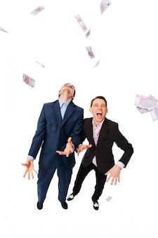 Uomini d'affari allegri lanciando un sacco di euro