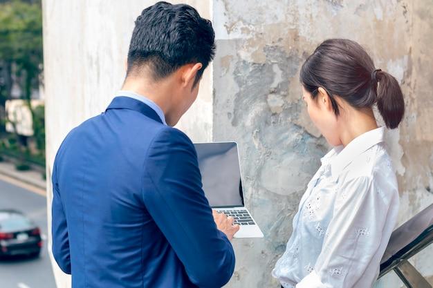 Uomini d'affari asiatici del gestore che discutono le idee con la donna di affari di riunione del computer portatile fuori. vista posteriore.