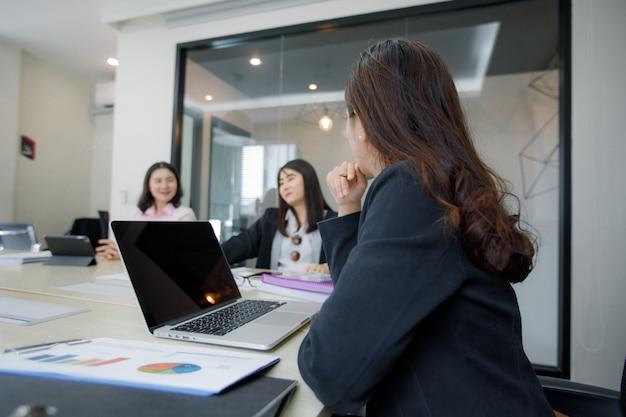 Uomini d'affari asiatici e gruppo usando il notebook per incontrarsi seriamente sul lavoro