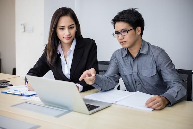 Uomini d'affari asiatici e gruppo utilizzando il notebook per partner commerciali discutendo documenti e idee in riunione e donne d'affari sorridendo felice per lavorare