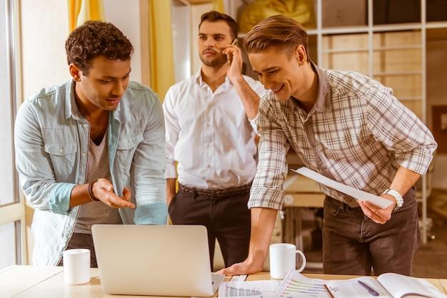 Uomini d'affari bei in abbigliamento casual che discutono insieme.