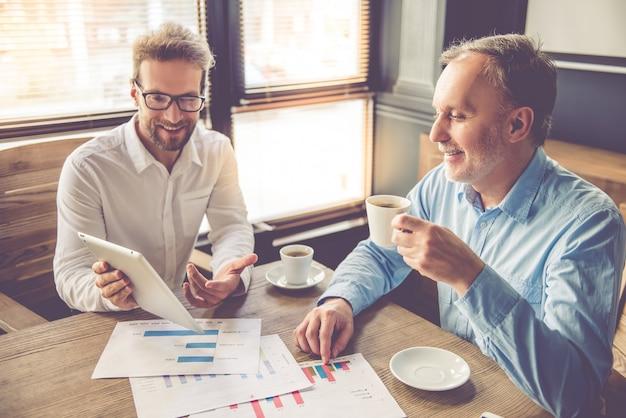 Uomini d'affari belli stanno usando una tavoletta digitale.
