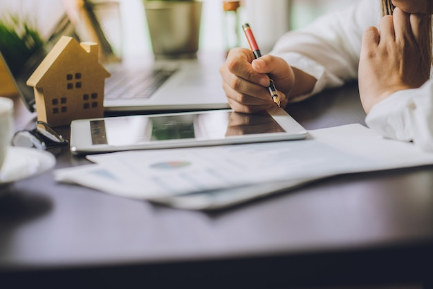 Uomini d'affari calcolando interessi, tasse e profitti da investire nel settore immobiliare e casa
