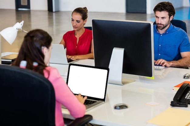 Uomini d'affari casuali che utilizzano computer portatili