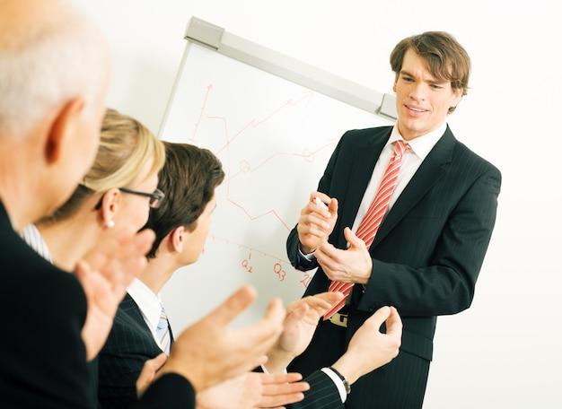Uomini d'affari che applaudono in una riunione