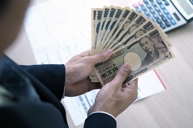 Uomini d'affari che contano le note di yen giapponesi nell'ufficio
