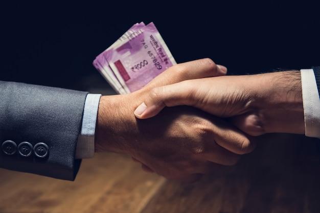 Uomini d'affari che fanno stretta di mano con soldi, valuta della rupia indiana, in mani