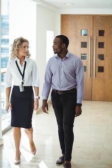 Uomini d'affari che hanno una discussione mentre camminano in corridoio