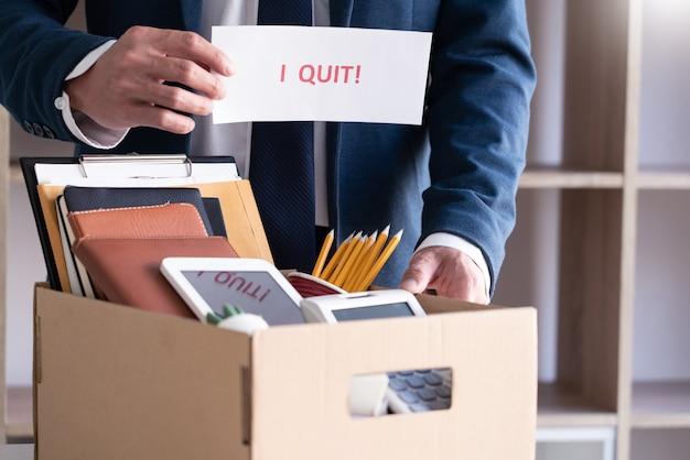 Uomini d'affari che mantengono le sue cose su una scatola di cartone con smettere di lettera