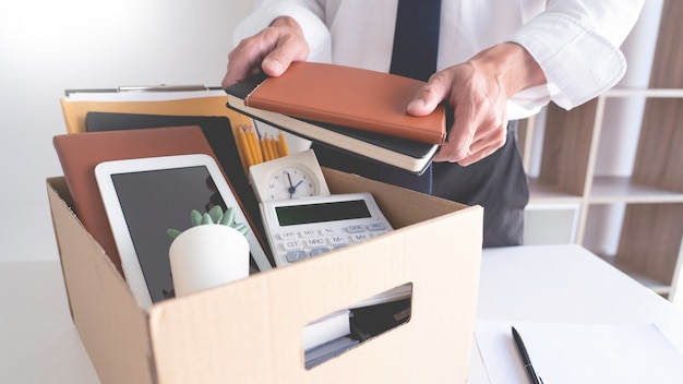 Uomini d'affari che tengono le sue cose su una scatola di cartone