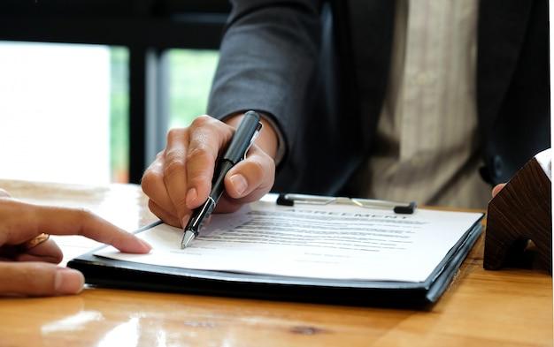 Uomini d'affari che vendono la casa indicando la firma del contratto di vendita in ufficio.