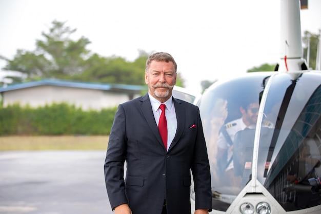 Uomini d'affari che viaggiano in elicottero, tiro di un uomo d'affari maturo utilizzando un auricolare mentre si viaggia in elicottero