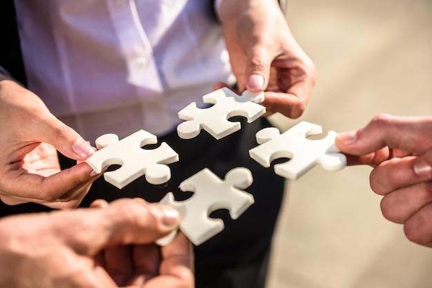 Uomini d'affari che vogliono mettere quattro pezzi di puzzle.