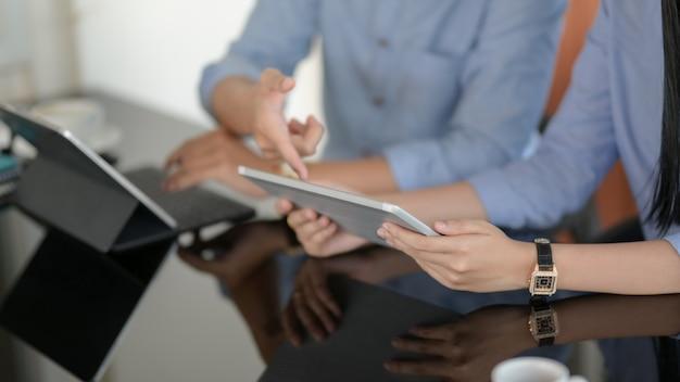Uomini d'affari consulenza sul loro progetto con tavolette digitali