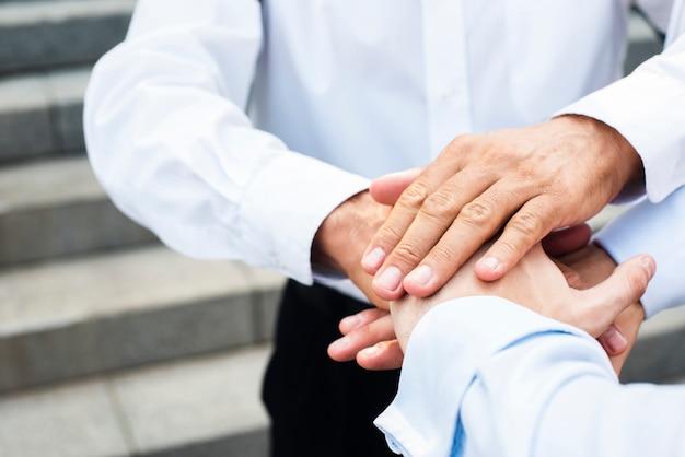 Uomini d'affari del primo piano che raccolgono le mani