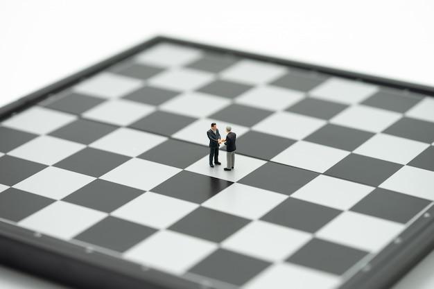 Uomini d'affari di miniatura 2 persone agitare le mani su una scacchiera con un gioco di scacchi