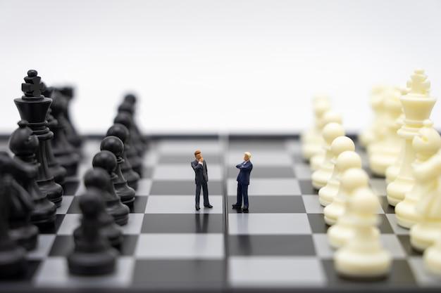 Uomini d'affari di persone in miniatura in piedi su una scacchiera con un pezzo degli scacchi