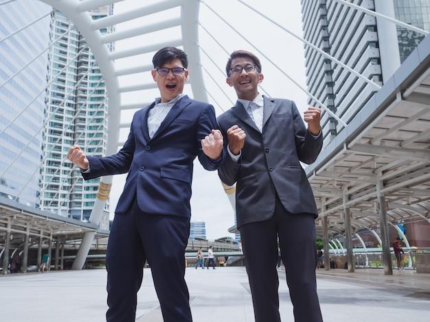 Uomini d'affari di successo con le braccia alzate celebrando la sua vittoria in città