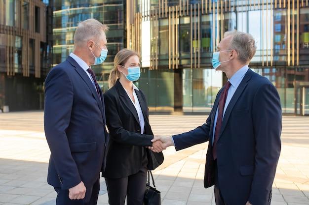 Uomini d'affari di successo in piedi vicino a edifici per uffici, si stringono la mano, si incontrano e parlano in città. primo piano, angolo basso. comunicazione e concetto di partenariato