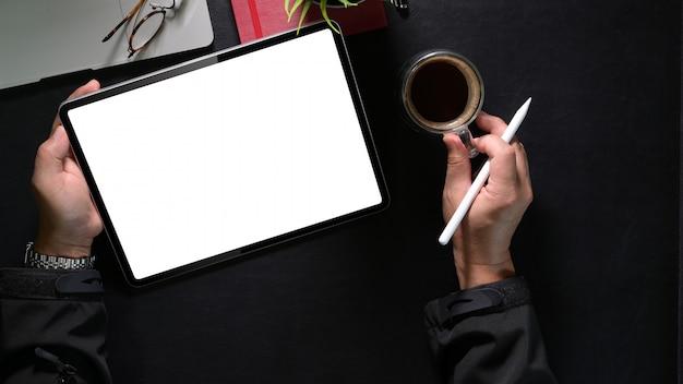 Uomini d'affari di vista superiore facendo uso della compressa digitale con la matita che guarda schermo in bianco in ufficio