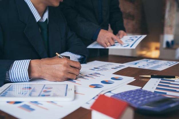 Uomini d'affari discutendo grafici e diagrammi che mostrano i risultati del lavoro di squadra dati e informazioni di successo.