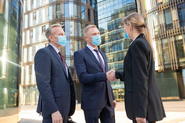 Uomini d'affari e donne in maschere per il viso che agitano le mani vicino a edifici per uffici, riunioni e parlare in città. vista laterale, angolo basso. concetto di cooperazione e coronavirus