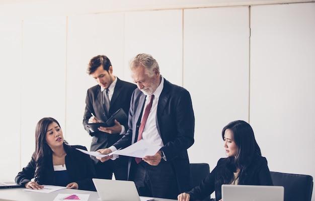 Uomini d'affari e gruppo che utilizzano il notebook per i partner che discutono di documenti e idee durante l'incontro