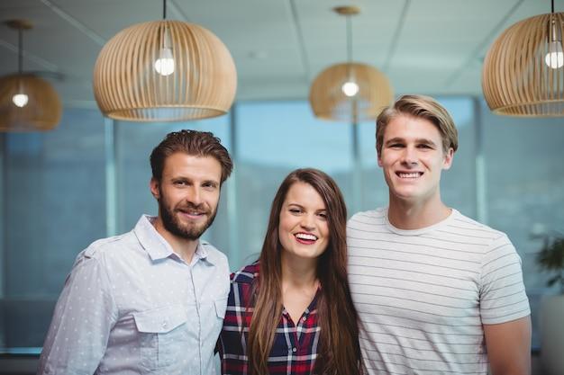 Uomini d'affari felici che stanno insieme nell'ufficio