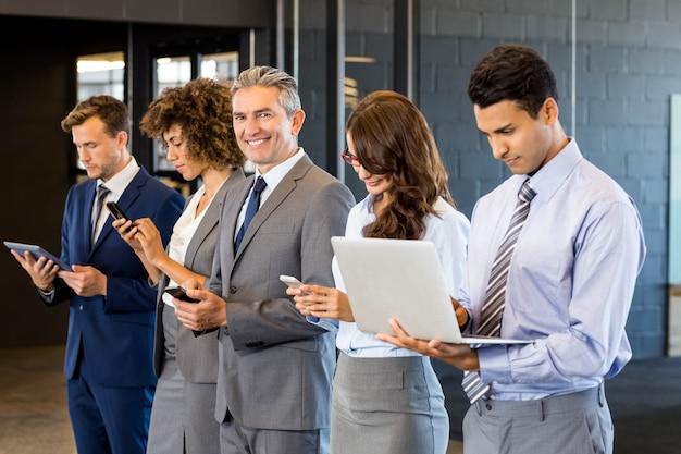 Uomini d'affari in fila e utilizzando il telefono cellulare, laptop e tablet digitale in ufficio