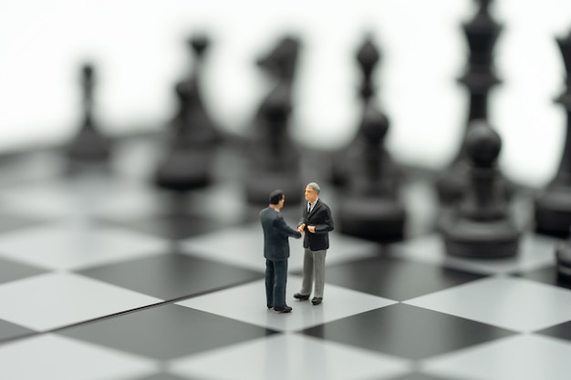 Uomini d'affari in miniatura 2 persone agita le mani su una scacchiera con un pezzo degli scacchi