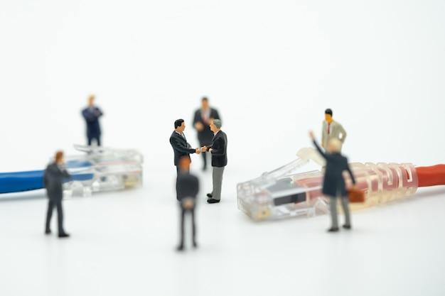 Uomini d'affari in miniatura 2 persone agitare le mani sul retro negoziare nel mondo degli affari.