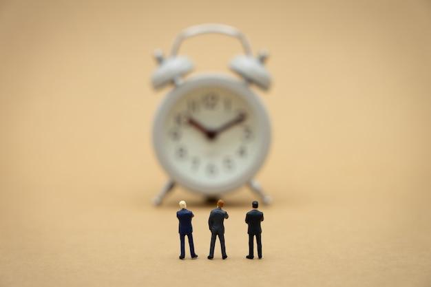 Uomini d'affari in miniatura 3 persone in piedi con la schiena negoziare nel mondo degli affari.