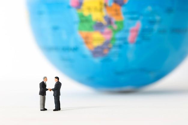 Uomini d'affari in miniatura che agitano le mani su sfondo sfocato globale o mondiale.